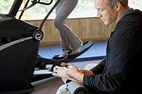 Personal trainer timing woman on fitness machine (thumbnail)