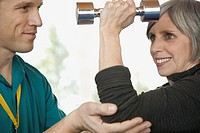 Personal trainer assisting middle_aged woman