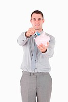Portrait of a young businessman putting a note in a piggy bank