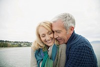 Mature couple cuddling on dock (thumbnail)