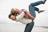 Mid_adult man lifting wife onto his back