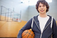 Male college student in gym with basketball