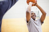 Male college student practicing basketball