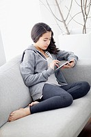 Teenage girl 13_15 sitting on sofa and using digital tablet