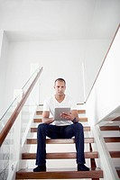 Man sitting on steps and using digital tablet
