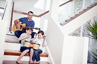 Young Father spending quality time time playing music for kids at home