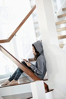 Young woman sitting on steps and using digital tablet