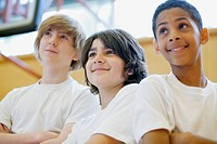 Three male teenage students posing in gymnasium