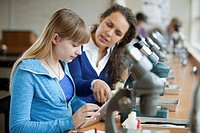 Teacher with student and microscopes.