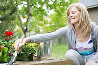Mature woman staining wooden flowerbed outdoors (thumbnail)