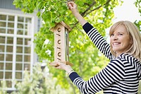 Mature woman hanging a bird feeder