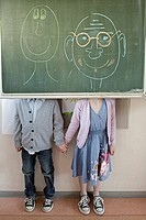Schoolboy and girl 6_7 standing behind blackboard with adult faces written on it