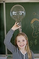 Happy young school girl 8_9 posing with large light bulb in front of blackboard