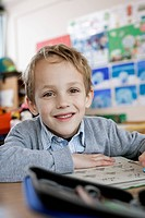 Happy school boy 8_9 sitting in class room