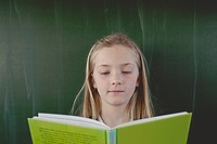 Happy young school girl 8_9 posing in front of blackboard with green book