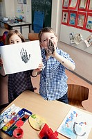 Girl 6-7 and boy 6-7 showing hand print during art class (thumbnail)