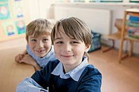 Two boys 8-9 posing in classroom (thumbnail)
