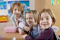 School boy 6_7 and two schoolgirls 6_7 sitting together in classroom