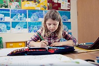 School girl 6_7 writing in classroom