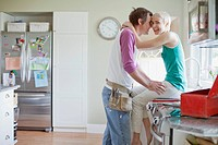 Mid adult couple being affectionate in kitchen.