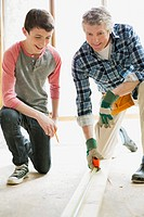 Father and teenage son doing home renovations (thumbnail)