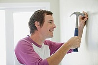 Mid adult male hammering nail in wall