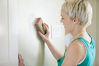 Pretty, mid adult woman sanding wall (thumbnail)