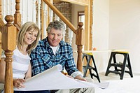 Middle aged couple reviewing renovation plans