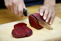 Hands chopping fresh beet on cutting board