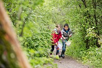 Elementary students chasing bugs on outdoor field trip