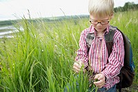 Elementary student examining grass on field trip
