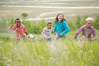 Elementary-aged children running in grassland (thumbnail)