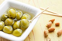 the green olives in ceramic bowl