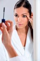 Brunette applying mascara