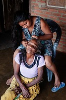 Young woman cleaning the hair of nits and fleas from an old woman, Waikkal village, Sri Lanka