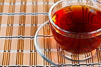 Teacup with black tea on straw napkin.