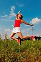 Frau springt auf einer Wiese vor Strommast