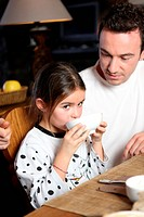 Man with little girl having breakfast