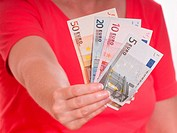 Weibliche Hand hält Euroscheine als Geldfächer nach vorne