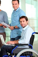 Young man in wheelchair at work