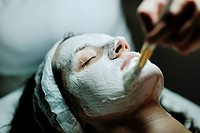 Young beautiful woman receiving cosmetic facial mask in spa beauty salon and relax