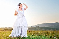 happy young beautiful bride after wedding ceremony event have fun on meadow in fashionable wedding dress
