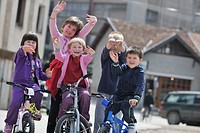 happy childrens group learning to drive bicycle outdoor at beautiful sunny spring day