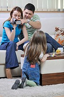 young happy family recording by video camera their child at home