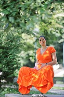 beautiful young happy pregnant woman outdoor in bright nature in orange dress