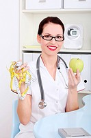 Female doctor holding apple and measuring tape.
