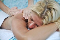 hands massaging her back _ A pretty woman getting a shoulder and back massage at spa and wellness center