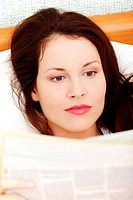 Beautiful woman reading a newspaper in bed.