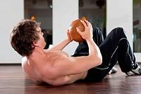 Mann trainiert mit Medizinball in Fitnessstudio