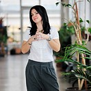 young happy business woman or student posing in fashionable clothes indoor in bright building